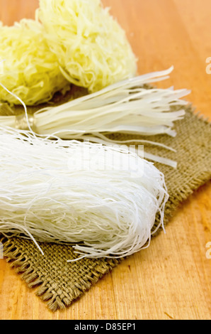 Different rice noodles on a coarse burlap napkin against a wooden board - Stock Photo