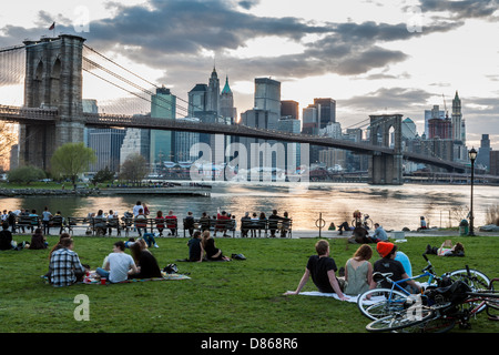 Families friends picnic on East River near Brooklyn Bridge in DUMBO neighborhood NYC - Stock Photo