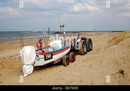 A view of an inshore fishing boat with trailer and tractor on the north-east coast of Norfolk at Eccles-on-Sea, - Stock Photo