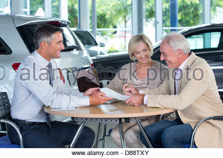 Salesman presenting contract to couple at table in car dealership showroom - Stock Photo