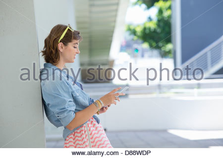 Young woman using digital tablet and leaning against wall - Stock Photo