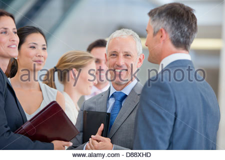 Portrait of smiling businessman among co-workers - Stock Photo