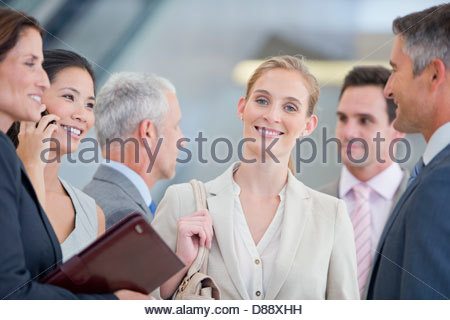Portrait of smiling businesswoman among co-workers - Stock Photo