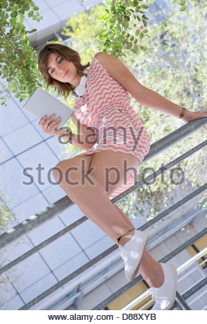 Young woman using digital tablet on railing - Stock Photo