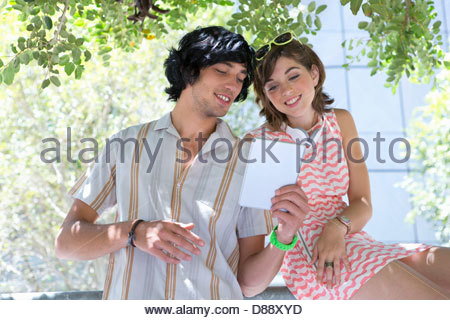 Smiling young couple using digital tablet - Stock Photo