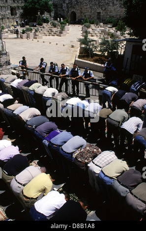 Israeli policemen stand guard as Palestinians men pray outside Al Akza mosque after banned to enter the Temple Mount - Stock Photo