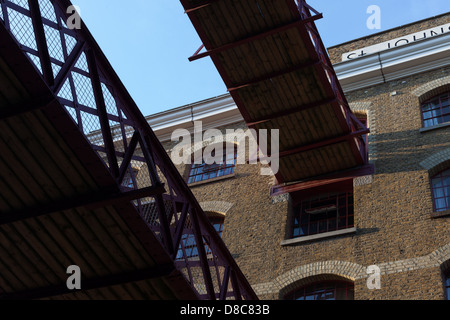 Dundee Court, Wapping High Street, showing old gangways above road originally used to move goods. - Stock Photo