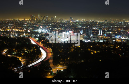 The city skyline viewed at night with smog with highway 101 in the foreground in Los Angeles, CA, USA (Adrien Veczan) - Stock Photo