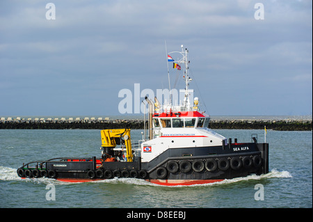 Tugboat Sea Alfa entering port on the North Sea, Netherlands - Stock Photo