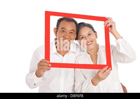 Old couple holding photo frame - Stock Photo