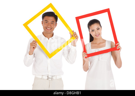 Young couple holding photo frame - Stock Photo