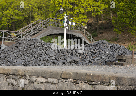 A pile of coal used in steam trains left on the railway sidings at a station. - Stock Photo