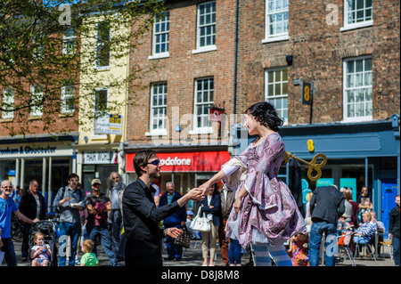 Imitating a clockwork music box dancer, Kate Mior interacts with a young man in her audience during the 2013 York - Stock Photo