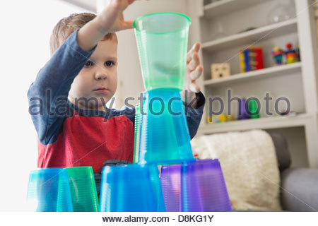 Boy playing with plastic cups at home - Stock Photo