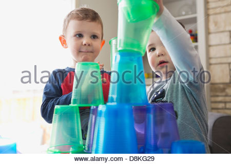 Boys playing with plastic cups at home - Stock Photo