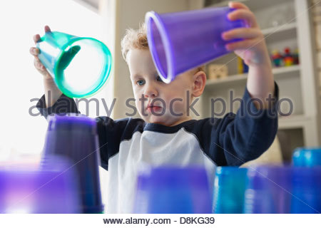 Young boy stacking plastic cups at home - Stock Photo