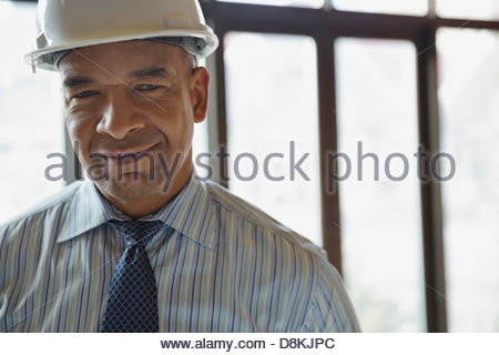 Portrait of male architect wearing hardhat at construction site - Stock Photo