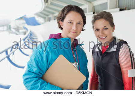 Portrait of female skeleton athlete and coach standing on track - Stock Photo