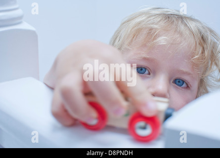 Little boy playing toy car on banister - Stock Photo