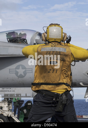 A US Navy sailor directs an F/A-18E Super Hornet fighter aircraft into position on the flight deck of the aircraft - Stock Photo