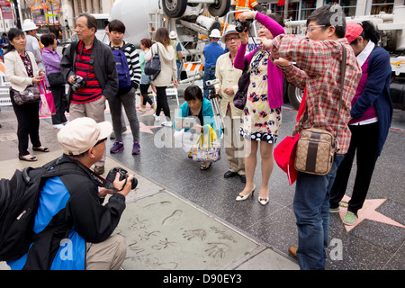 Asian tourists on sidewalk at Hollywood walk of Fame outside Mann's Chinese theater in Hollywood Los Angeles California - Stock Photo