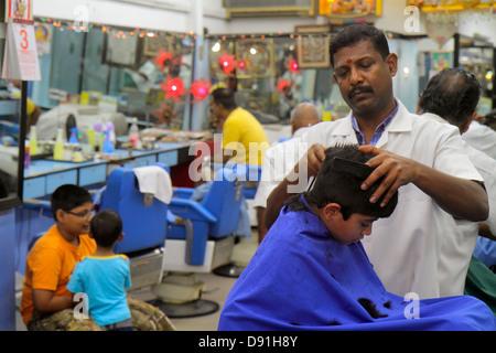 Singapore Little India Serangoon Road Asian man barber shop inside interior business boy haircut bindi - Stock Photo