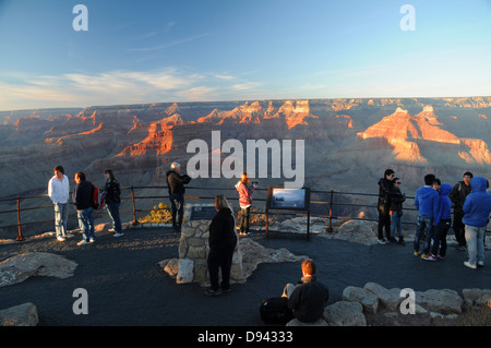 Visitors at overview lookout area on South Rim of Grand Canyon National Park in Arizona at sunset - Stock Photo