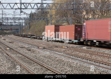 Freight containers speeding along the West Coast Main Line through Tamworth Railway Station. - Stock Photo