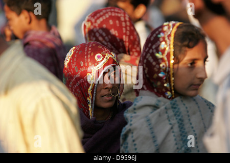 Tribal Rajasthani woman with traditional nose ring standing in the crowd of men, Rajasthan, India - Stock Photo
