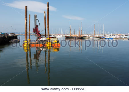 Floating platform gets into position to drive piles into the harbour bed for a new ferry pontoon, Brixham, Devon - Stock Photo