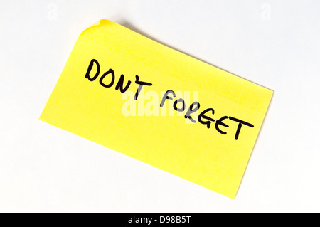 Don't Forget written in capital letters on a yellow post it note. - Stock Photo