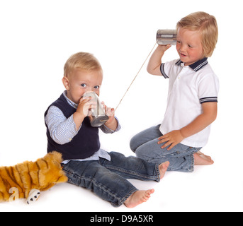 Two little brothers talking on the phone using two cans and a piece of rope - Stock Photo