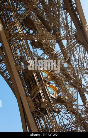 Two bright orange elevators climbing Eiffel Tower girder as tourists walk down adjacent steps - Stock Photo