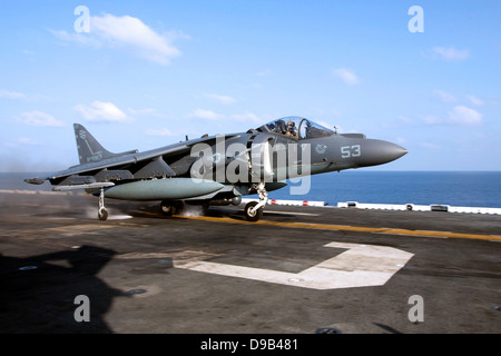 A US Marine Corps AV-8B Harrier fighter aircraft takes off from the flight deck of the amphibious assault ship USS - Stock Photo