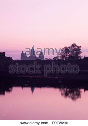 The silhouette of Angkor Wat seen across the moat at sunrise, Siem Reap Province, Cambodia - Stock Photo