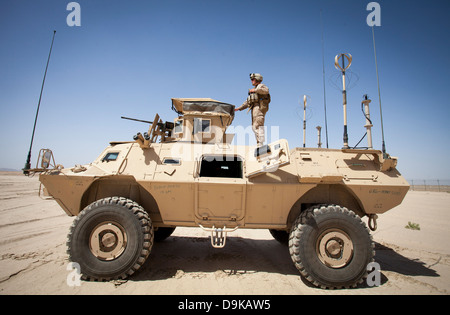 A US Marine Corps advisor stands on a M1117 armored vehicle to observe Afghan National Army special operations Force - Stock Photo