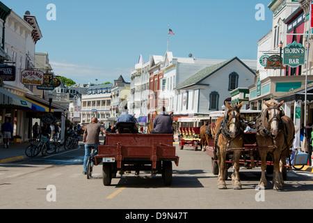 Michigan, Mackinac Island. Typical horse carriage in downtown Mackinac on Main Street (aka Huron). - Stock Photo