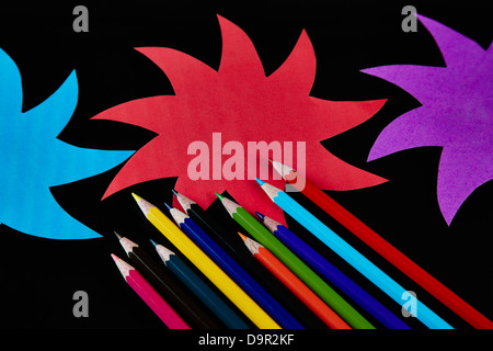 Coloured paper stars with color pencils on black background - Stock Photo