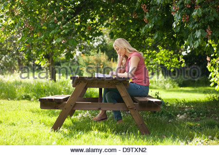 A young woman sitting on a garden bench reading a book - Stock Photo