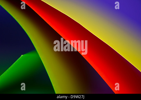 Macro and abstract image of colored cardstock (red,yellow and green) with a curved shape on a blue background. - Stock Photo
