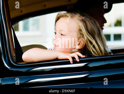 Little girl leaning out the window of a car - Stock Photo