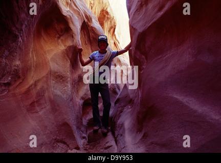 USA, Utah, Grand Staircase-Escalante National Monument, Man hiking through Rustler's Gulch Slot Canyon - Stock Photo