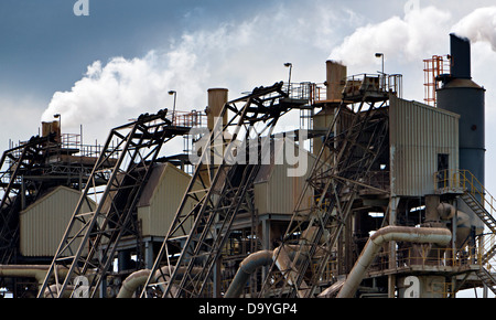Smoke emerging from chimneys at a stone crushing plant in Cumbria, England - Stock Photo
