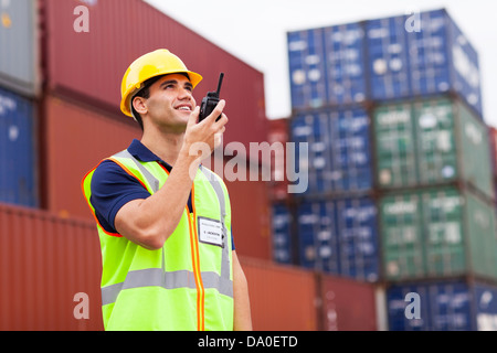 young harbor worker talking on the walkie-talkie at container warehouse - Stock Photo