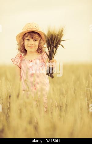 Happy child in autumn wheat field - Stock Photo