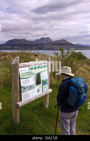 Walker reading Forestry Commission sign, Leitir Fura, Kinloch forest, Isle of Skye, UK. - Stock Photo