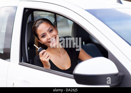 happy young woman showing a car key inside her just bought new vehicle - Stock Photo
