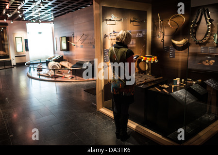 BRUSSELS, Belgium - A visitor looks at a display case of various cultural instruments from around the world on display - Stock Photo