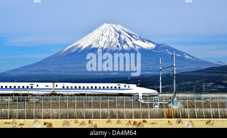 A bullet train passes below Mt. Fuji in Japan. - Stock Photo