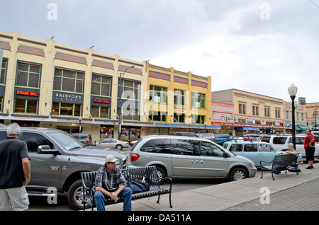 Downtown buildings cars and pedestrians in Prescott, Arizona, USA. Several shops and restaurants line the main street. - Stock Photo